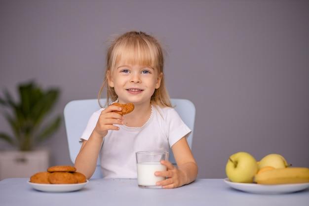 Menina bonitinha comendo biscoitos e bebendo leite em casa ou no jardim de infância