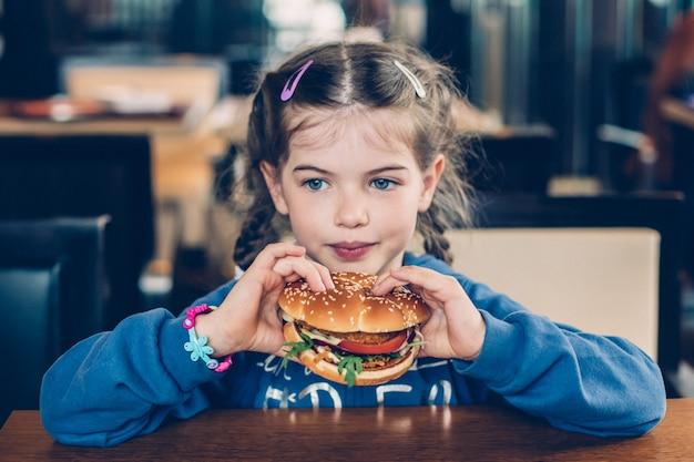 Menina bonitinha comendo hambúrguer de fast food em um café