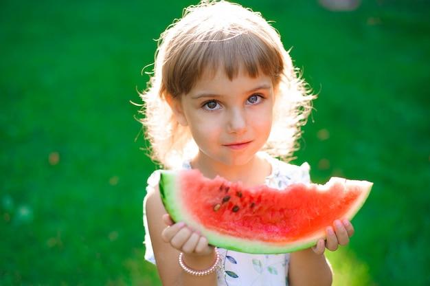 Menina bonitinha comendo melancia e desfrutando de piquenique