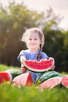 Menina bonitinha comendo melancia na grama no verão. criança, comida saudável.