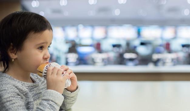 Menina bonitinha comendo um hambúrguer no fast food