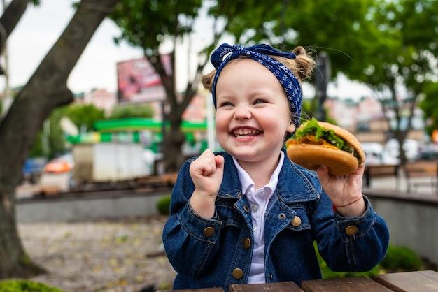 Menina bonitinha comendo um hambúrguer no restaurante