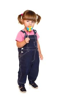 Menina bonitinha comendo um pirulito colorido