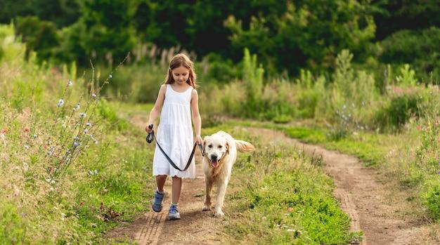 Menina bonitinha correndo com um cachorro adorável na estrada no verão