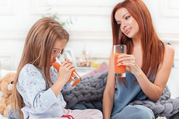 Menina bonitinha curtindo, brincando e criando com suco com a mãe