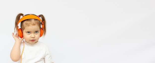 Menina bonitinha curtindo música usando fones de ouvido, isolado sobre o branco