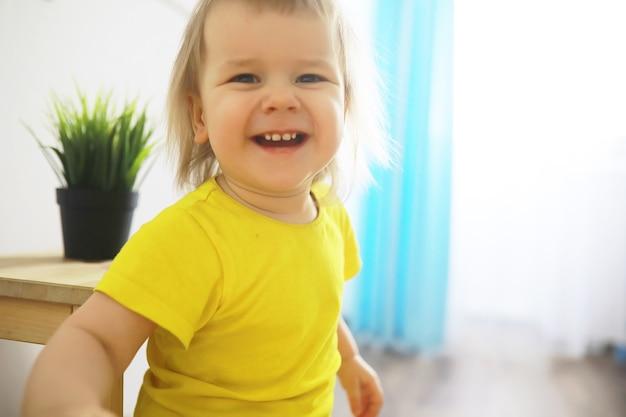 Menina bonitinha da criança se divertindo segurando o pote com flores plantadas em casa. flor e conceito de cuidado da natureza. crianças e família infância feliz.