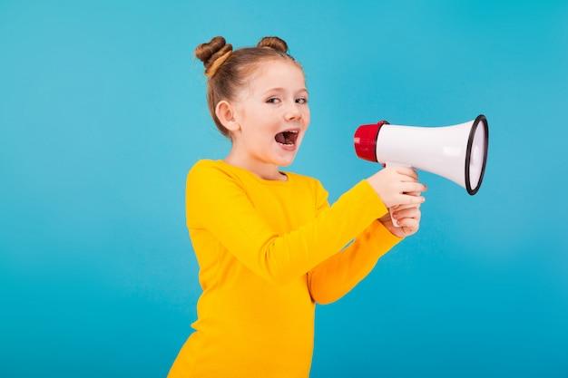 Menina bonitinha de camisola amarela com o alto-falante