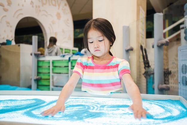 Menina bonitinha de etnia asiática tirando fotos de areia azul com as mãos enquanto passa um tempo no quarto das crianças