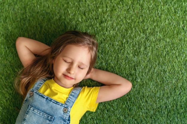 Menina bonitinha de macacão jeans, deitado no tapete verde, gramado fechou os olhos