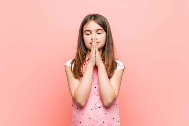 Menina bonitinha de mãos dadas em rezar perto da boca, sente-se confiante.