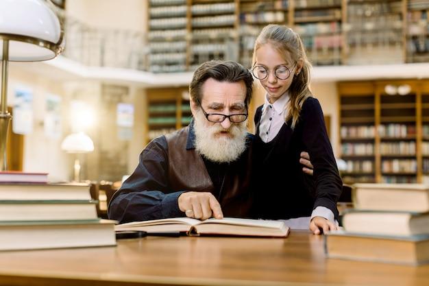 Menina bonitinha de óculos à mesa na biblioteca antiga, abraçando o avô e lendo o livro juntos