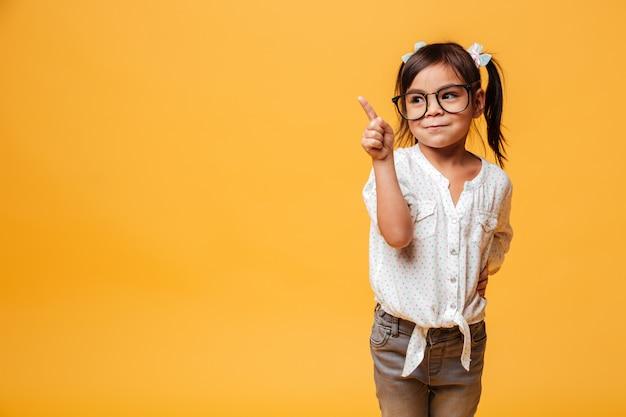 Menina bonitinha de óculos apontando.