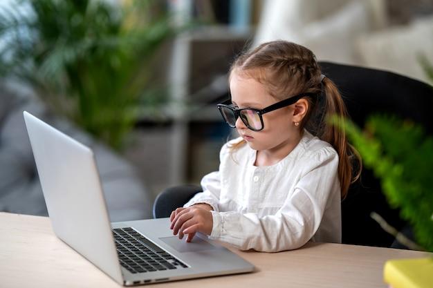 Menina bonitinha de óculos está aprendendo usando o laptop. conceito de e-learning