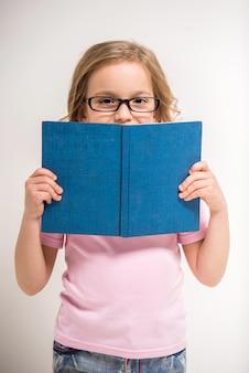 Menina bonitinha de óculos está segurando um livro.