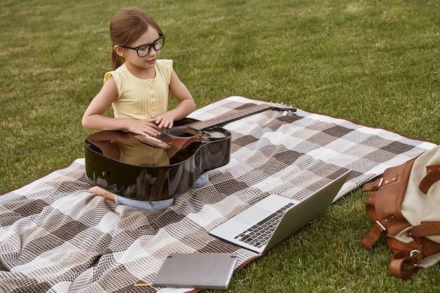 Menina bonitinha de óculos, sentada em uma grama verde no parque, segurando um violão