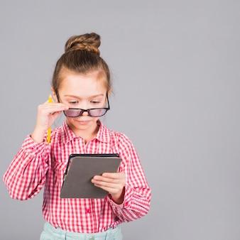 Menina bonitinha de óculos usando tablet