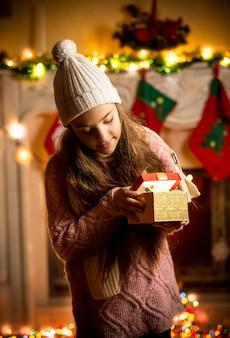 Menina bonitinha de suéter olhando para uma caixa de presente na véspera de natal