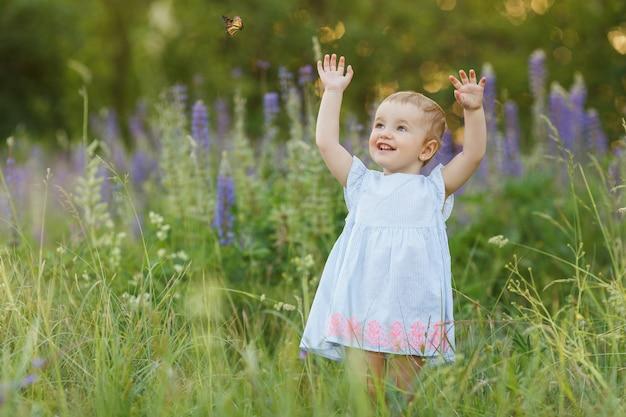 Menina bonitinha de vestido azul tentando pegar uma borboleta