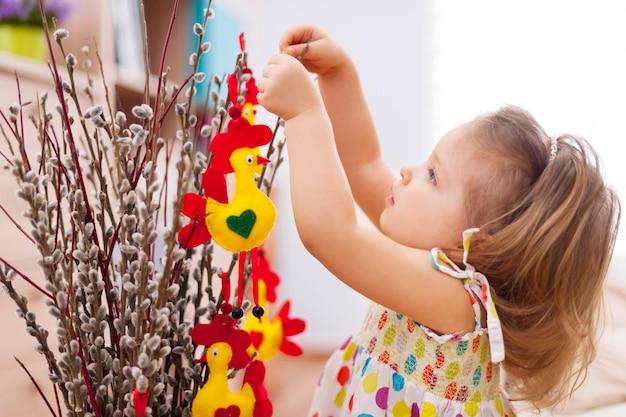 Menina bonitinha decorando a casa para a páscoa