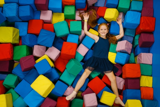 Menina bonitinha deitada em cubos macios, playground no centro de entretenimento.