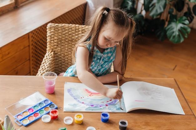 Menina bonitinha desenha com um pincel e pinta na mesa da sala de estar
