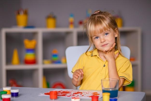 Menina bonitinha desenhando com tintas no jardim de infância