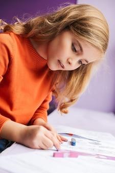 Menina bonitinha desenhando em um livro para colorir dentro de casa