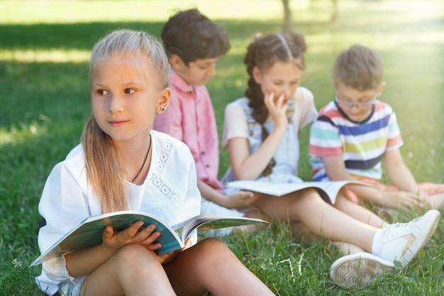 Menina bonitinha desviando o olhar pensativamente enquanto lê ao ar livre com seus colegas de classe