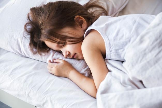 Menina bonitinha dormindo em sua cama em casa