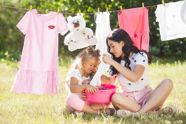 Menina bonitinha e a mãe lavando roupa