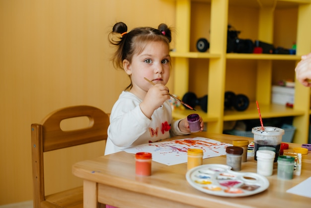 Menina bonitinha é brincar e pintar no quarto dela.