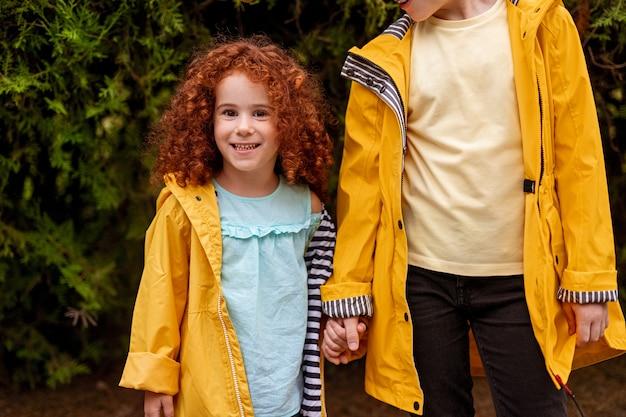 Menina bonitinha e irmãozinho em capas de chuva sorrindo juntos na floresta
