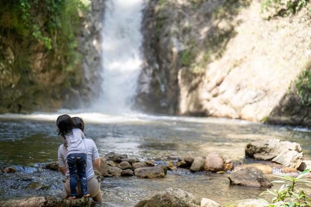 Menina bonitinha e mãe sentadas perto da cascata de água