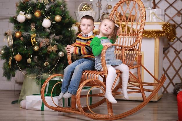 Menina bonitinha e menino sentado na cadeira de balanço perto da árvore de natal.
