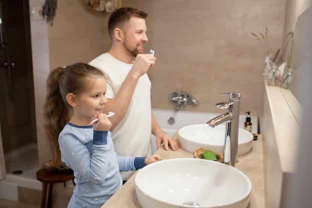 Menina bonitinha e seu jovem pai feliz com escovas de dente indo escovar os dentes em pé no banheiro em frente ao espelho