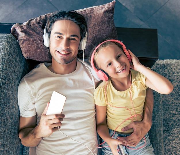 Menina bonitinha e seu pai bonito em fones de ouvido.