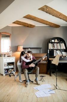 Menina bonitinha e seu pai bonito estão tocando guitarra