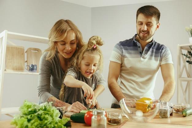 Menina bonitinha e seus lindos pais estão cortando legumes e sorrindo enquanto fazem salada na cozinha em casa. conceito de estilo de vida familiar