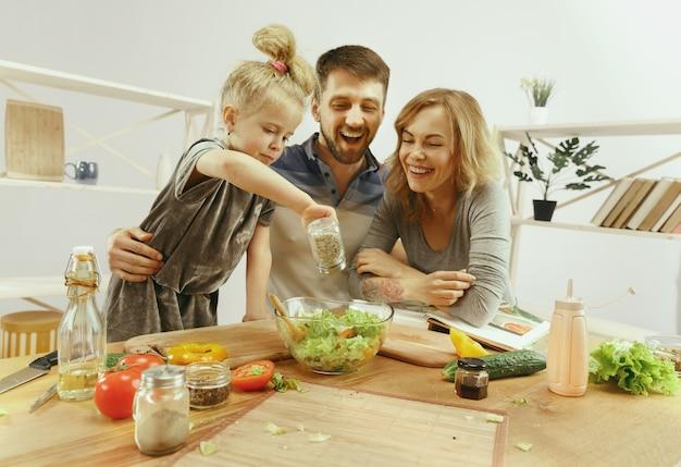Menina bonitinha e seus lindos pais estão cortando vegetais e sorrindo enquanto fazem salada na cozinha de casa