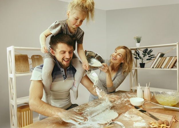 Menina bonitinha e seus lindos pais preparando a massa para o bolo na cozinha de casa