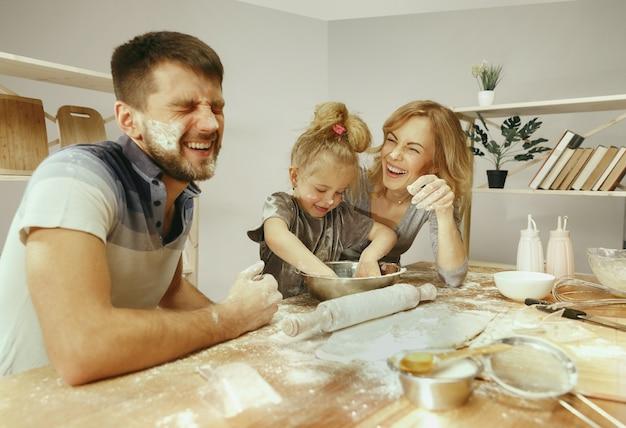 Menina bonitinha e seus lindos pais preparando a massa para o bolo na cozinha em casa. conceito de estilo de vida familiar