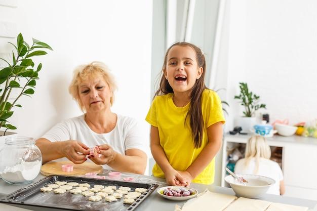 Menina bonitinha e sua avó fazem biscoitos na cozinha.