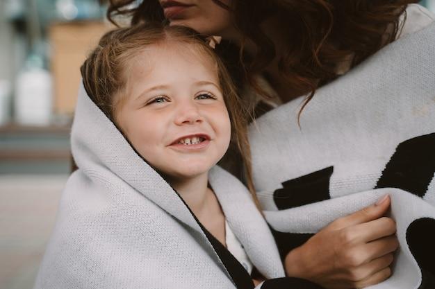 Menina bonitinha e sua linda jovem mãe se abraçam, ao ar livre