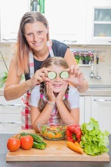 Menina bonitinha e sua linda mãe estão brincando e sorrindo enquanto coocking na cozinha em casa
