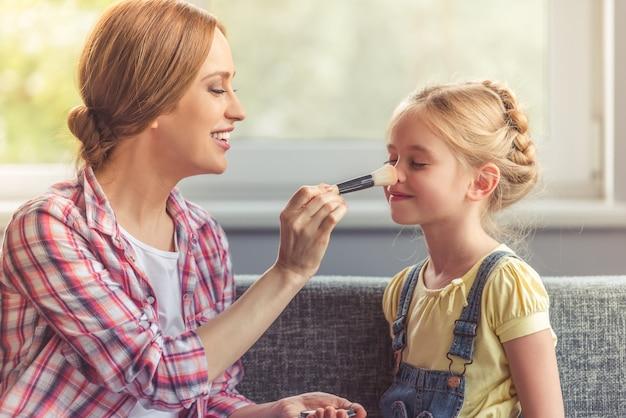 Menina bonitinha e sua linda mãe estão fazendo maquiagem