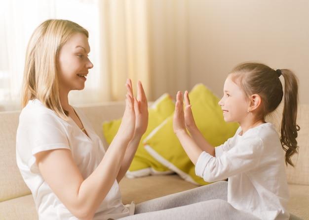 Menina bonitinha e sua linda mãe estão jogando jogos em casa, batendo palmas.