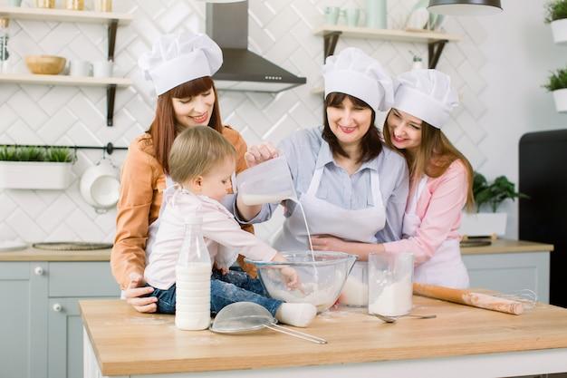 Menina bonitinha e sua linda mãe, tia e avó em aventais e chapéus se divertindo ao derramar leite para farinha e amassar a massa na cozinha moderna em sweet home. mulheres assando na cozinha