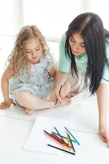 Menina bonitinha e sua mãe desenhando uma foto juntos dentro de casa.