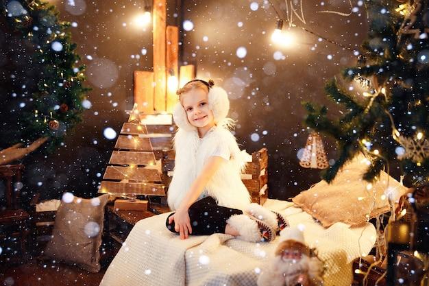 Menina bonitinha em abafador de pele sentado perto de árvore de natal